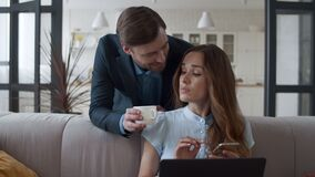 Loving family couple making coffee break at home. Man bringing tea cups to wife.