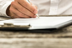 Closeup low angle view of male hand signing subscription form, l Stock Photo