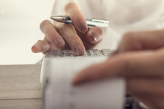 Closeup low angle view of a woman using a manual adding machine. To do the accounts in the office, vintage effect toned image royalty free stock image