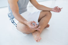 Closeup low section of a man sitting in lotus pose Royalty Free Stock Images