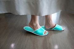 Closeup low section of a person`s feet wearing green slipper wal stock photos