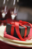 Closeup of luxury present against champagne glasses bokeh. Royalty Free Stock Image