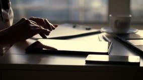 Closeup mörk kontur av kvinnliga händer hon skriver något i minnestavla, är därefter en kopp, mobilen, bärbar dator på tabellen stock video