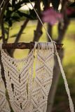 Closeup of macrame art. Hanging from the piece of driftwood, shot with shallow depth of field Royalty Free Stock Photo