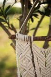 Closeup of macrame art. Hanging from the piece of driftwood, shot with shallow depth of field Royalty Free Stock Photography