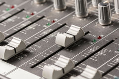 Closeup macro audio mixing console knobs and sliders. Stock Photos