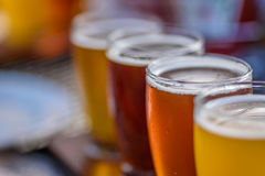 Closeup macro of a beer flight in sunlight. Low angle view of colorful beer flight glasses outside in the bright sunlight Stock Photo
