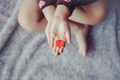 Macro of child with adult parent hands palms holding a bunch of small red and purple paper foam hearts. Closeup macro of child with adult parent hands palms Stock Image