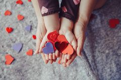 Macro of child with adult parent hands palms holding a bunch of small red and purple paper foam hearts. Closeup macro of child with adult parent hands palms Stock Photos