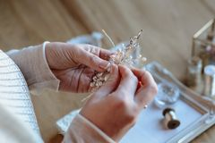 Closeup macro photo of details, workplace of decorator and creator of wedding imitation jewelry. Woman`s hands in a process of creation stock photo