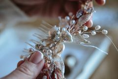 Closeup macro photo of details, workplace of decorator and creator of wedding imitation jewelry. Woman`s hands in a process of creation stock images