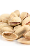 Closeup macro roasted pistachio over white background Stock Photos
