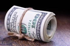 Closeup, macro of rolled American dollar banknotes. Wooden background. Pile of cash Stock Images