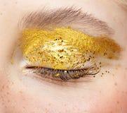 Closeup macro shot of closed human female eye with yellow smoky eyes beauty makeup. Closeup macro shot of closed human female eye. Woman with unusual glitter stock images