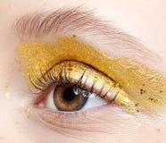 Closeup macro shot of human female eye with yellow smoky eyes beauty makeup. Closeup macro shot of human female eye. Woman with unusual glitter glitzy vogue face royalty free stock image