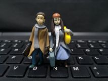 Closeup and macro shot of miniature working people with their suitcase and a computer background. royalty free stock photography
