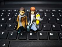 Closeup and macro shot of miniature working people with their suitcase and a computer background. stock images