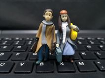 Closeup and macro shot of miniature working people with their suitcase and a computer background. royalty free stock photo