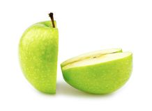 Closeup macro of two halves of a perfectly cut green apple. Detailed stock photography