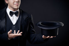 Closeup of magician showing tricks with top hat. Isolated on dark background Stock Photo