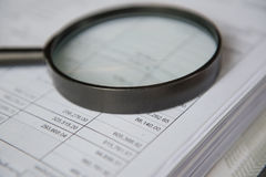 Closeup magnifying glass with finance business sheet stock images