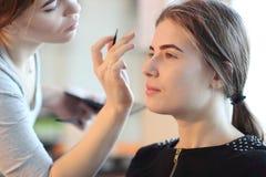 Closeup of a makeup artist applying makeup Stock Photography