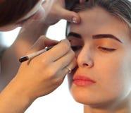 Closeup of a makeup artist applying makeup Stock Images
