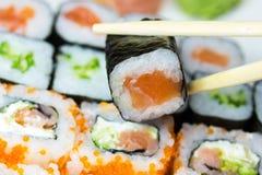 Closeup of maki sushi. Closeup view of a set of maki sushi. One piece of sushi is in the sushi bars royalty free stock photos