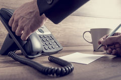 Closeup of male assistant about to answer a telephone call Royalty Free Stock Images