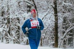 Closeup male athlete senior years running in winter woods Stock Image