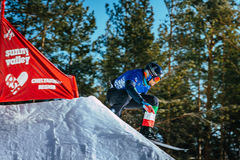 Closeup male athlete snowboarder jumps from a springboard Stock Photo