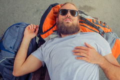 Closeup of male backpacker tourist napping on a bench. Closeup of handsome male backpacker tourist napping on a bench and baggage at the station Stock Photo