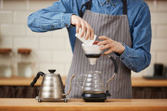 Closeup of male barista pouring ground coffee making pourover. Stock Photography