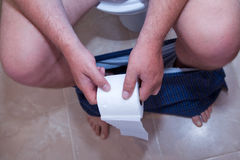 Closeup of male body parts while sitting on the toilet. Holding in hands roll of toilet paper Stock Images