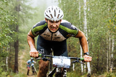 Closeup of a male cyclist rides through forest, he has a dirty face Royalty Free Stock Photo