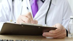 Closeup of male doctor hand writing a medical prescription. stock video footage