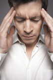 Closeup Of Male Executive With Fingers Pressed To Forehead Stock Photography