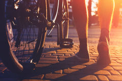 Closeup Of Male Feet And City Bicycle Wheels, Rear View And Low Angle Holiday Weekend Activity. Legs of a man in sneakers and a city bicycle are moving about the Royalty Free Stock Photo