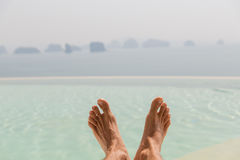 Closeup of male feet over sea and sky on beach. Summer holidays, beach, travel, leisure and body care concept - closeup of male feet over sea and sky Royalty Free Stock Image