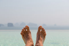 Closeup of male feet over sea and sky on beach Royalty Free Stock Photos