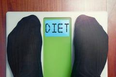 Closeup male feet on scale Diet word. Closeup male feet on scale at morning Diet word Stock Image