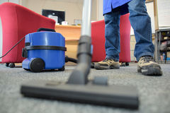 Closeup male feet and vacuum cleaner Royalty Free Stock Photo