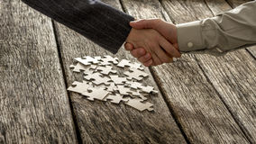 Closeup of male and female business partners shaking hands over Stock Photography