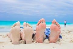 Closeup male and female feet on white sand. Close up male and female feet on white sand beach Stock Photo