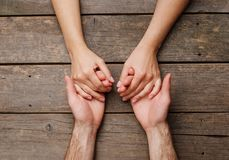 Closeup of male and female hands on rustic wooden background stock photo