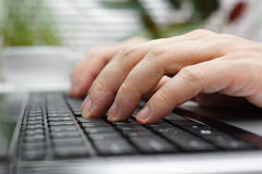 Closeup of male fingers on laptop keyboard Royalty Free Stock Image