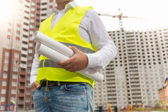 Closeup of male foreman holding rolled blueprints Stock Photos