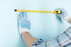 Closeup of male in gloves measuring wall with tape Royalty Free Stock Images
