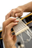 Closeup of male guitarist playing black jazz electric guitar Royalty Free Stock Photos