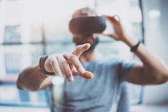 Closeup of male hand.Bearded young man wearing virtual reality goggles in modern coworking studio. Smartphone using with. VR headset in office. Horizontal stock photography